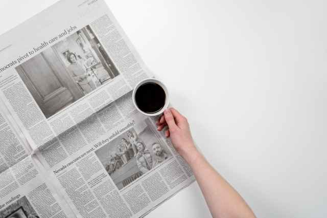 person holding white ceramic mug on newspaper