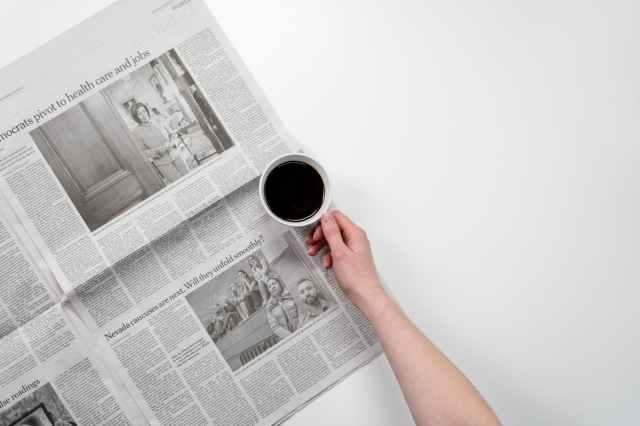 person holding white ceramic mug on newspaper